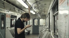 Man using mobile and typing a message phone in metro wagon, subway transportation public wi fi. Busy tired man. Man using mobile and typing a message phone in stock video footage