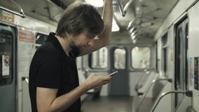 Man using mobile and typing a message phone in metro wagon, subway transportation public wi fi. Busy tired man. Man using mobile and typing a message phone in stock footage