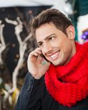 Man Using Mobilephone In Christmas Store. Happy young man using mobilephone in Christmas store Stock Photos