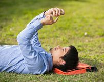 Man Using Mobilephone While Lying On Grass At. Side view of young man using mobilephone while lying on grass at college campus Stock Photography