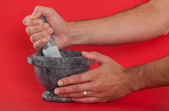 Man using a mortar and pestle. Close up of a man using a mortar and pestle Stock Photo