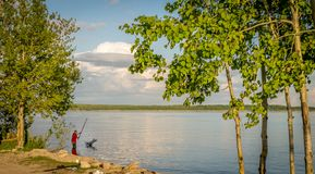 A man using a net to fish in reservoir on a sunny day. stock photography