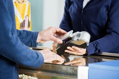 Man Using NFC Technology At Concession Counter. Midsection of men using NFC technology to pay bill at concession counter in cinema Royalty Free Stock Images