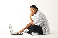 Man using a notebook computer. Young African American man using a notebook computer on a white background royalty free stock images