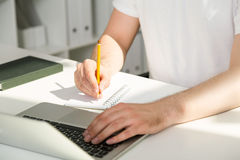 Man using notebook and writing. Closeup of man's hands using laptop and writing in notepad with pencil Royalty Free Stock Photo