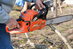 A man is using an orange chainsaw to cut tree branches Stock Image