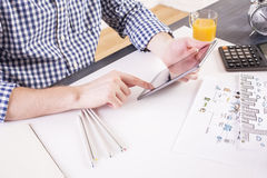 Man using pad side. Side view of man in casual shirt using pad at office desk with business sketch, calculator and orange juice and pencils Stock Image