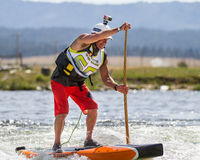 Man using a paddleboard to get down the river Stock Photos
