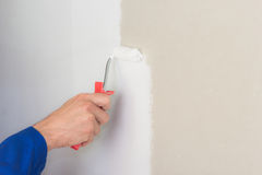 Man using paint roller on the wall Stock Photo