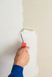 Man using paint roller on the wall Stock Photography