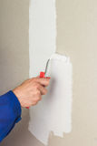 Man using paint roller on the wall Stock Images