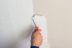 Man using paint roller on the wall Royalty Free Stock Images