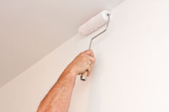 Man using paint roller on white wall Royalty Free Stock Image