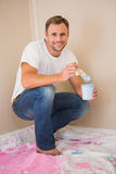 Man using paintbrush to paint wall blue Stock Image