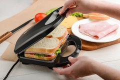 Man using a panini press. Close up shot. Easy making of grilled sandwiches for a breakfast stock image