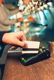 Man using payment terminal. White credit card. Hand use credit card. Bar table. The beer taps in a pub. Costumer concept. Service concept Royalty Free Stock Photo