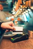 Man using payment terminal. White credit card. Hand use credit card. Bar table. The beer taps in a pub. Costumer concept. Service concept Stock Images