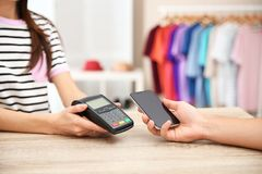 Man using payment terminal with smartphone in shop, closeup. Space for text royalty free stock image
