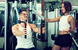 Man using pec deck gym machinery. Cheerful well trained men using pec deck gym machinery while listening to girlfriend  indoors Royalty Free Stock Image