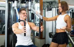 Man using pec deck gym machinery. Cheerful well trained men using pec deck gym machinery while listening to girlfriend  indoors Stock Photography