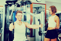Man using pec deck gym machinery. Happy well trained men using pec deck gym machinery while listening to girlfriend  indoors Royalty Free Stock Photos
