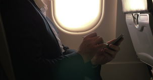 Man using pen to type on smart phone in plane stock footage