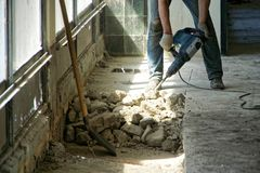 A man using a perforator dismantles the cement floor in a room with large windows. Daylight royalty free stock image