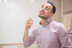 Man using perfume before date Stock Photography