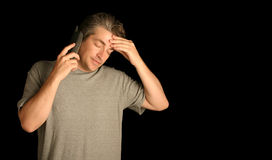 Man using a phone. Man looking stressed using a  phone on a black background Stock Photos