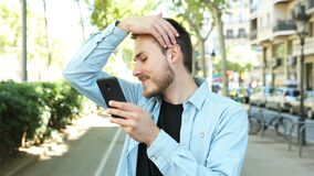Man using a phone as a mirror to comb himself stock footage