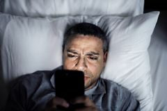 Man using phone on a bed stock photography