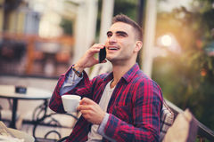 Man using phone in a cafe. Young man using phone in a cafe Royalty Free Stock Images
