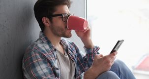 Man using phone while drinking coffee stock video footage