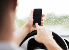 Man using phone while driving the car Stock Image