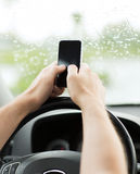 Man using phone while driving the car Stock Images
