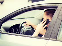 Man using phone while driving the car Stock Photos