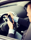 Man using phone while driving the car Royalty Free Stock Photos