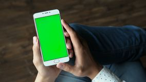Man using phone with green screen hold in hands. Human arms hold electronics gadget with chromakey touchpad closeup. Guy gesturing: tapping and scrolling app by stock footage