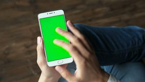 Man using phone with green screen hold in hands. One guy holding in arms electronics gadget with greenscreen touchpad, scrolling and tapping on the knee close up stock footage