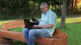 Man using phone and laptop in the park. In summer day stock video