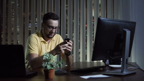 Man using phone in office at night. Man texting with phone and smiling while sitting in office and having overtime stock footage