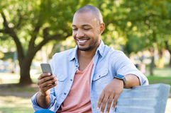 Man using phone outdoor. Young african man sitting at park and using smart phone. Happy smiling guy reading a message on cellphone while sitting on a bench in a Stock Photo