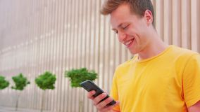 Man Using a Phone Outdoors. A young man using a phone outdoors royalty free stock image