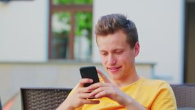 Man Using a Phone Outdoors. A young man using a phone outdoors royalty free stock photos