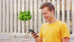 Man Using a Phone Outdoors. A young man using a phone outdoors stock images