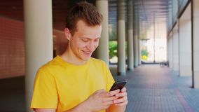 Man Using a Phone Outdoors. A young man using a phone outdoors stock photos
