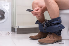 Man using phone while sitting on a toilet bowl. Man wearing jeans and shoes using phone while sitting on a toilet bowl in  the modern tiled bathroom at home Royalty Free Stock Image