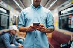 Man using phone in subway car, addicted people. Young man using phone in subway car, addiction problem, social addicted people, modern underground lifestyle royalty free stock photography