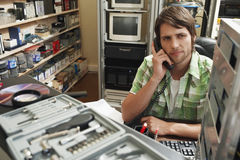 Man Using Phone Surrounded By Computer Equipment Royalty Free Stock Images