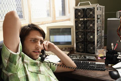 Man Using Phone Surrounded By Computer Equipment. Young man using landline phone surrounded by computer equipment Royalty Free Stock Image